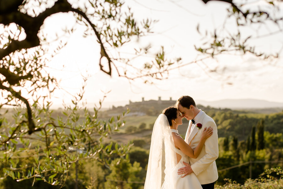 bride and groom intimate moment at borgo stomennano with monteriggioni in the background