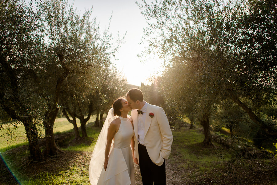 bride and groom walking in a olive trees road during the golden hour
