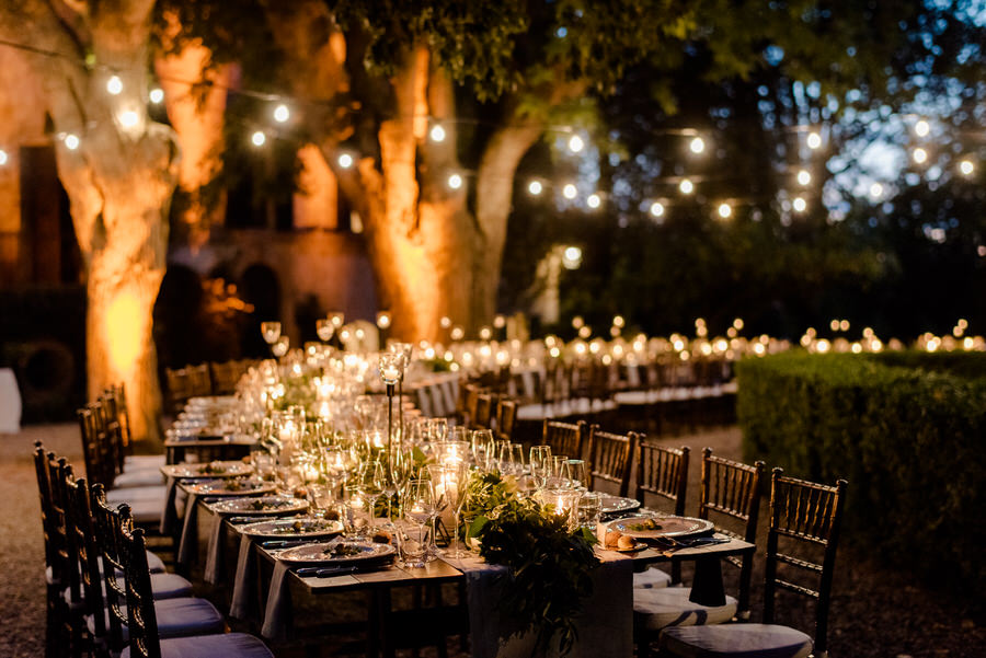 amazing wedding table decorated with flowers, candels and string lights