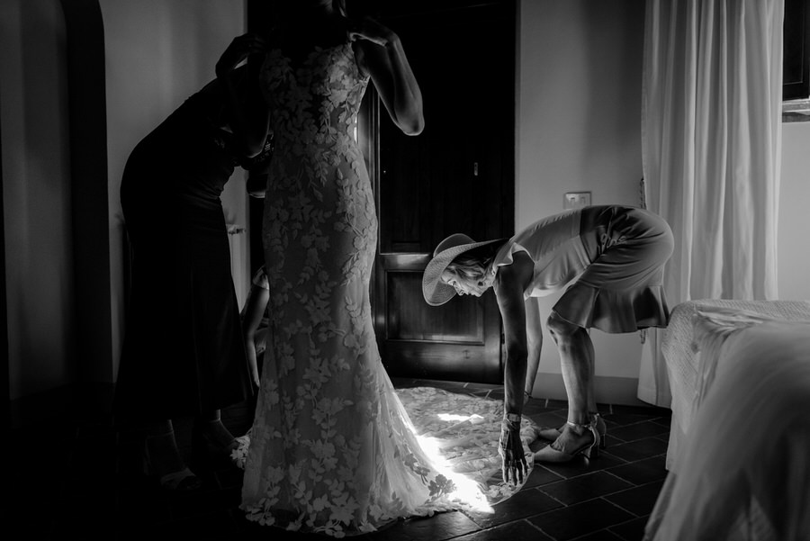 mother helping his daughter to wear the bridal dress