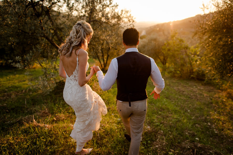 wedding couple walking seen from behind in tuscany at Borgo i Vicelli Florence during the golden hour