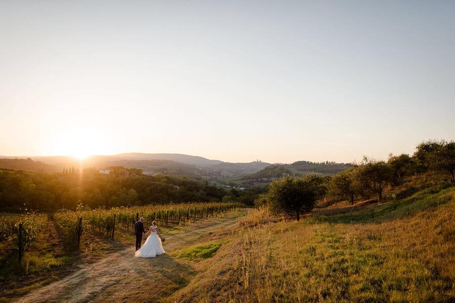 couple walking at the golden hour in Tuscany with a beautiful view