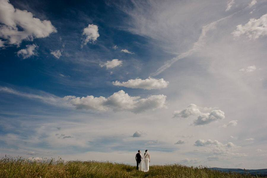 wedding couple walking in a field in tuscany with the blue sky