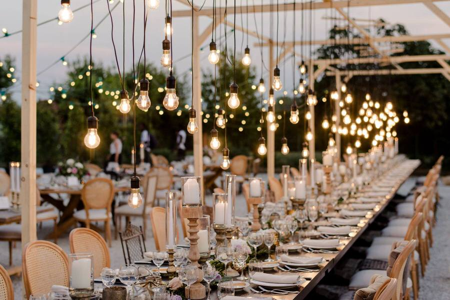 wedding dinner with a long table decorated with candles and bulb lights