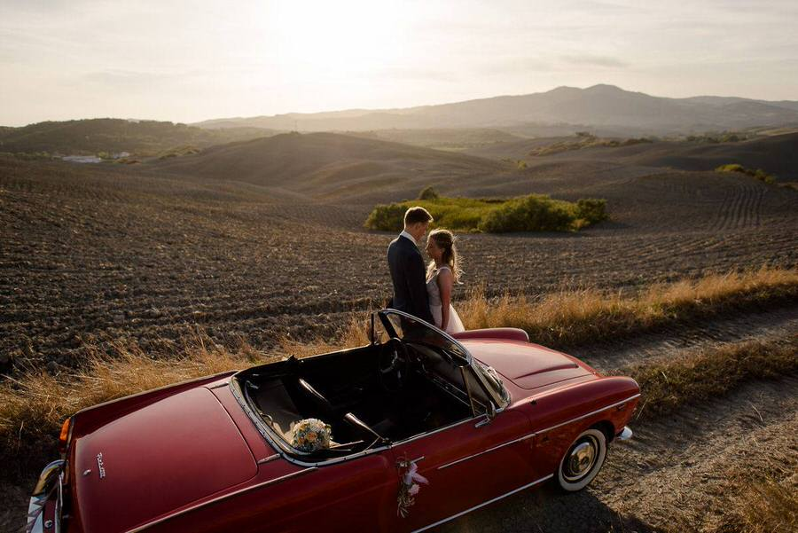 wedding couple in tuscany with a vintage red car