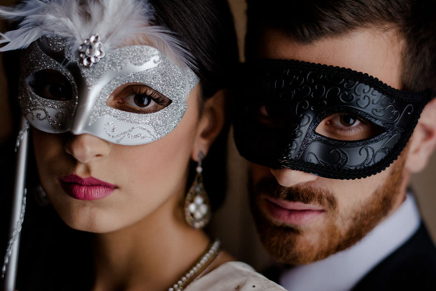 bride and groom with theatrical masks