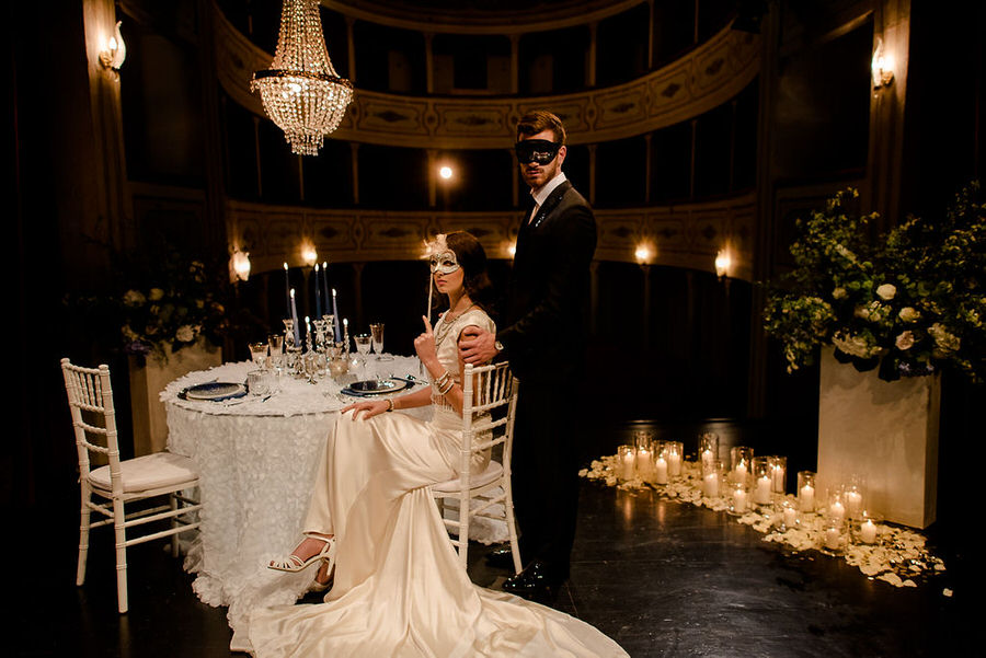 wedding table in a theather bride and groom with theatrical masks