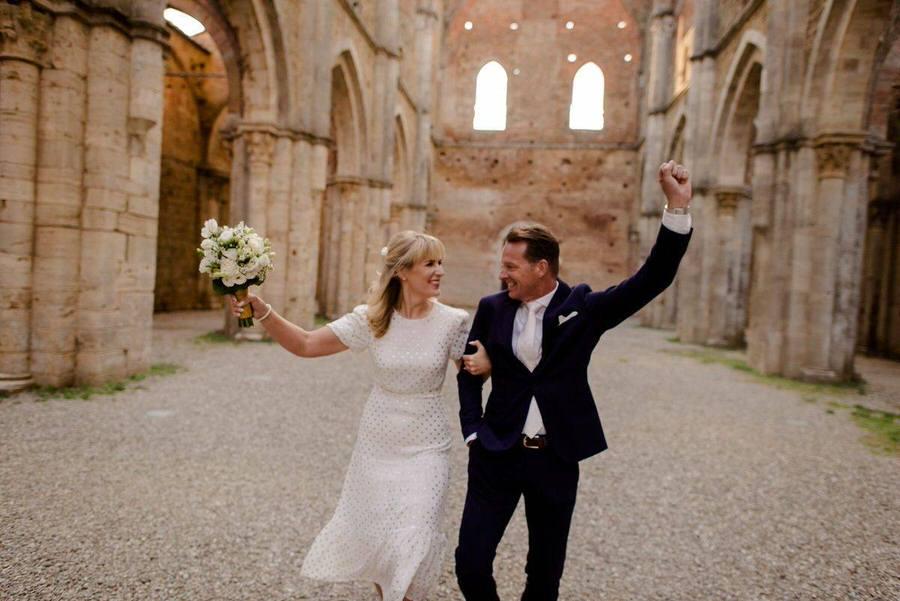 happy wedding couple at san galgano abbey in tuscany
